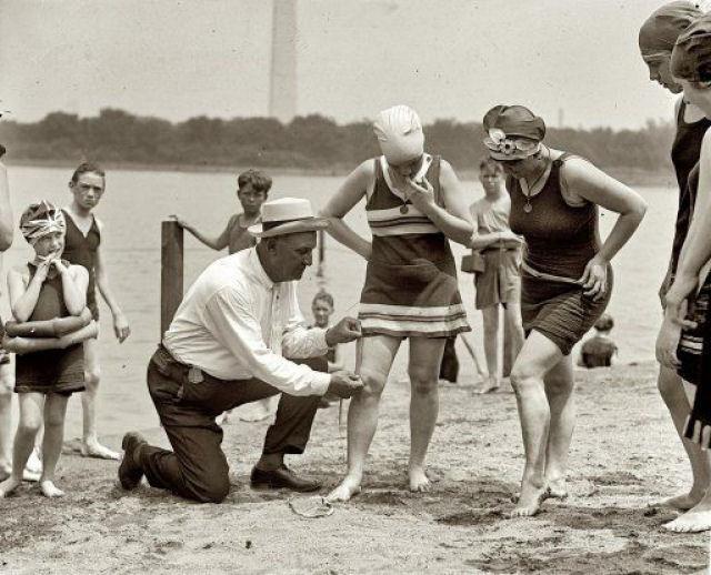 Homem mede o tamanho do biquíni da mulher com uma régua na praia.