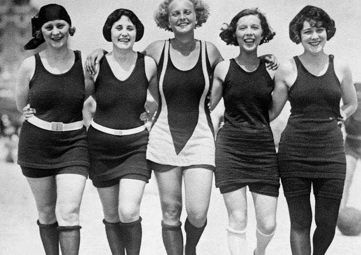 cinco mulheres provavelmente da década de 1920 usam maio da época. Os modelos são longos, chegam a coxa e mostram pouco o corpo da mulher.